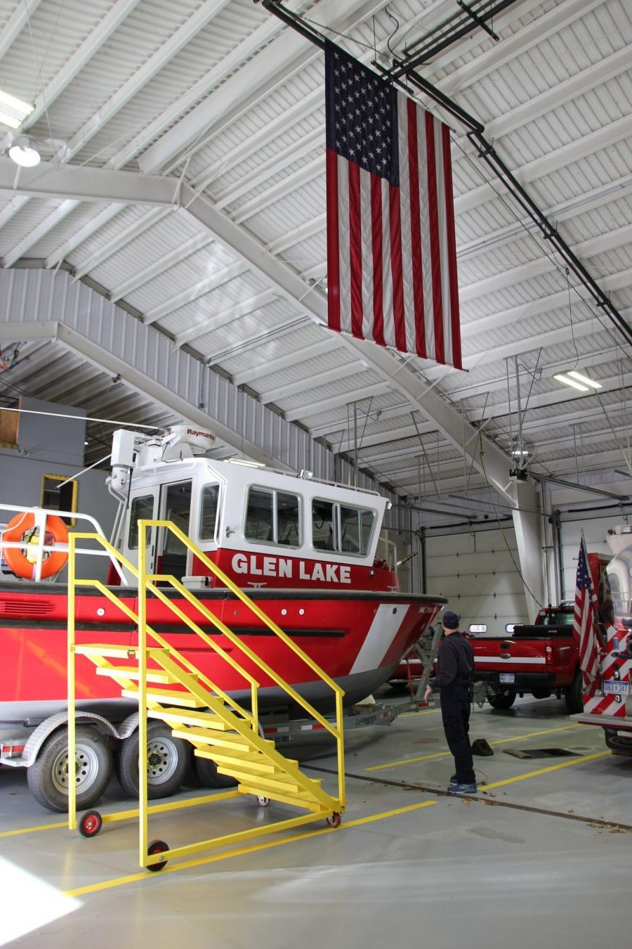 inside of station, vehicles parked, american flag haning from ceiling